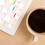 Workplace with tablet pc showing calendar and a cup of coffee on
