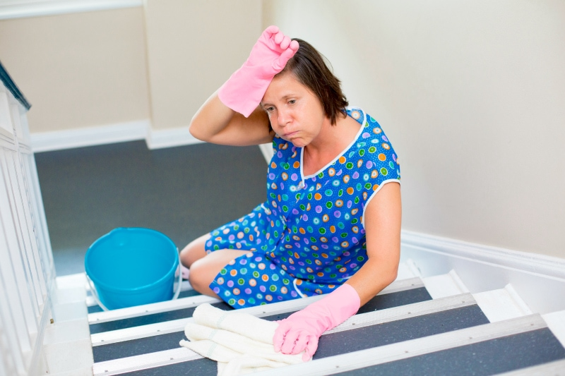 woman cleaning staircase and looking exhausted
