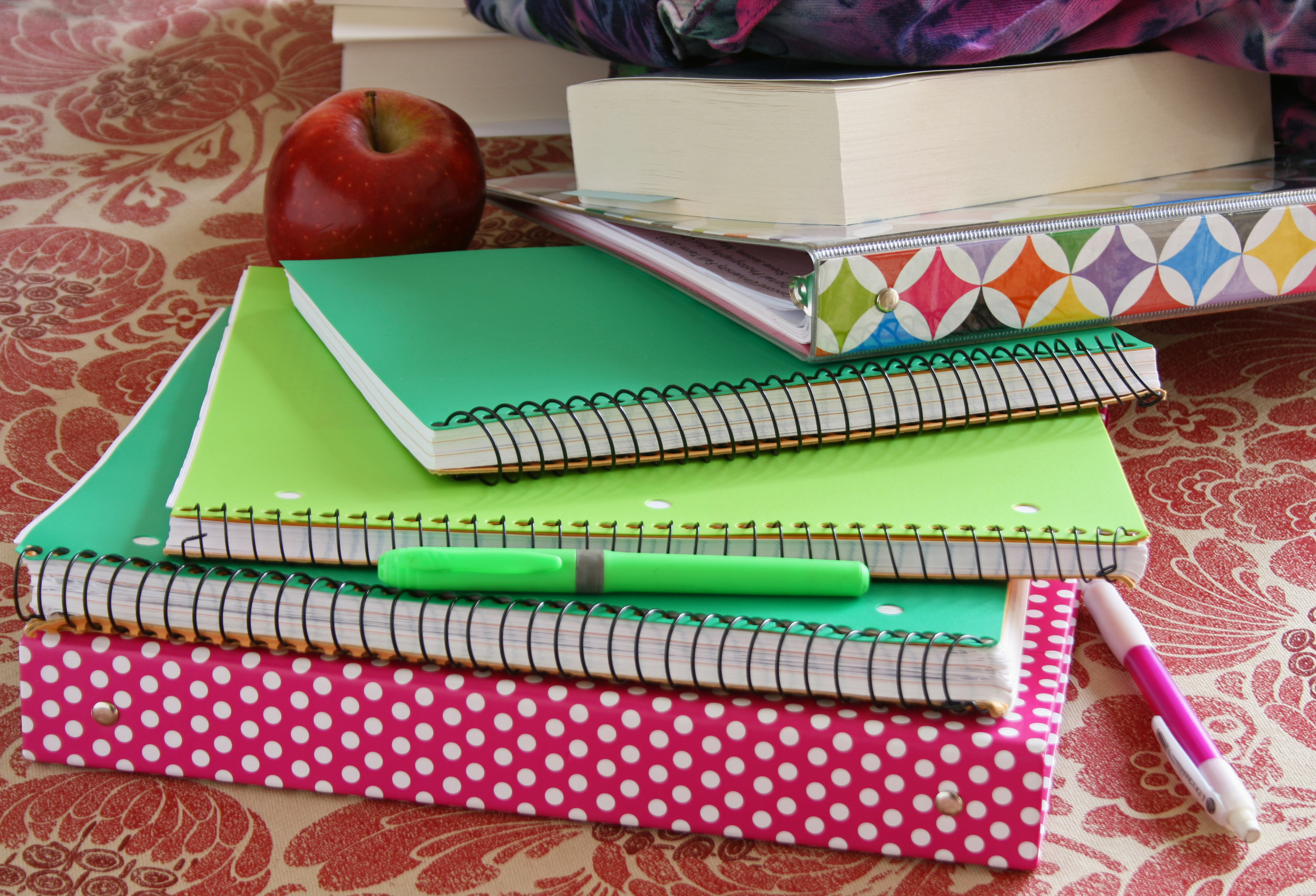 Closeup of school notebooks on a table with an apple