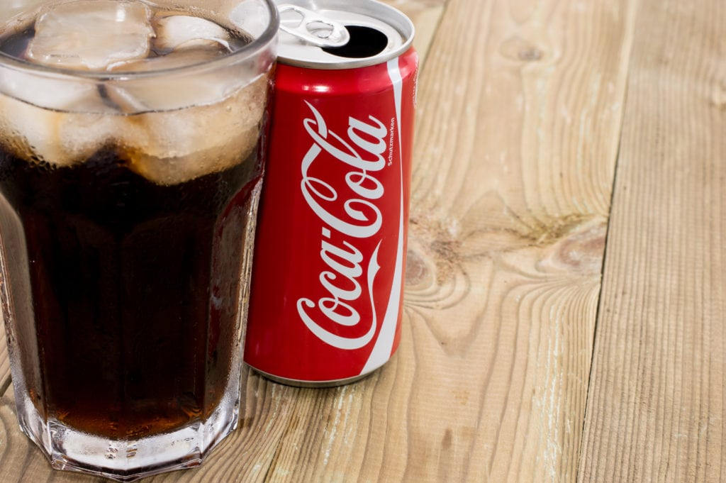 Coca Cola can with Cola in a glass